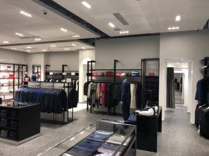 Inside a Hugo Boss store displaying suits and belts alternative angle