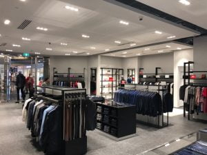 Inside a Hugo Boss store displaying suits and belts