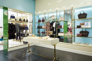 Wide shot of the inside of a Kate Spade New York store showing handbags along the wall