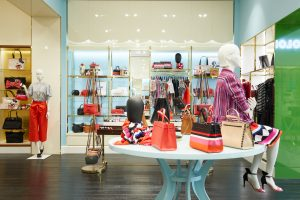 Photo of a mannequin sitting on the edge of a table in front of display clothes and handbags