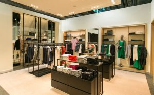 the inside of a Hugo Boss clothing store with a mannequin in a green dress